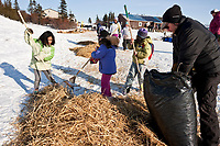 Volunteer checker Brad VanMeter helps clean up Sebastian Schnuelle's used straw with local 7 & 8 year old school kids at Koyuk in Arctic Alaska during the 2010 Iditarod