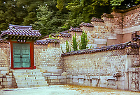 A fine art landscape image of a traditional garden in Seoul, Korea.  The gate on the left has a bright red border with steps leading down into a courtyard.  The gate doors are green iron.  The doorway and surrounding walls are topped with traditional tiles.