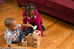 21 month old toddler boy with 7 year old sister playing with pound a ball maze toy using wooden mallet to hit ball