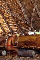 Hawaiian man wearing malo, carving contemporary Hawaiian sailing canoe under a thatched hale at Puuhonua o Honaunau National Historic Park in Kona, Big Island of Hawaii