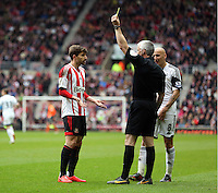 Pictured L-R: Fabio Borini of Sunderland sees a yellow card by match referee Chris Foy for protesting against his decision to award a foul against team mate Santiago Vergini. Sunday 11 May 2014<br /> Re: Barclay's Premier League, Sunderland v Swansea City FC at the Stadium of Light, Sunderland, UK.