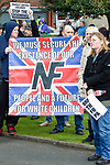 """© Joel Goodman - 07973 332324 . 03/03/2012 . Heywood , UK . Protesters hold up a National Front banner with a 14 words quote from David Lane , """" We must secure the existence of our people and a future for white children """" . The National Front hold a rally in protest against an alleged paedophile ring that had been operating in the area . There is currently (3rd March 2012) a case being tried at Liverpool Crown Court in relation to the allegations . Last Thursday (23rd February 2012) a protest organised in the town in relation to the same story resulted in Asian business being attacked by an angry mob . Photo credit : Joel Goodman"""