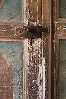 A detail of a rustic painted door with an iron key and lock.