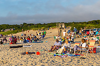 People gather and wait on Menemsha beach to view the sunset over the Vineyard Sound in Chilmark, Massachusetts on Martha's Vineyard.