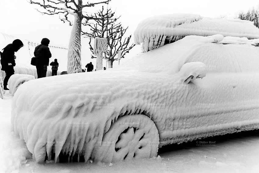 Switzerland. Canton Geneva. Versoix. Frozen car. The car has been parked close to the lake. The wind blew lake's water on the car which froze and is totally stuck in the ice. Tourists take pictures. The town of Versoix is distant 10 km from Geneva. 12.02.2012 © 2012 Didier Ruef