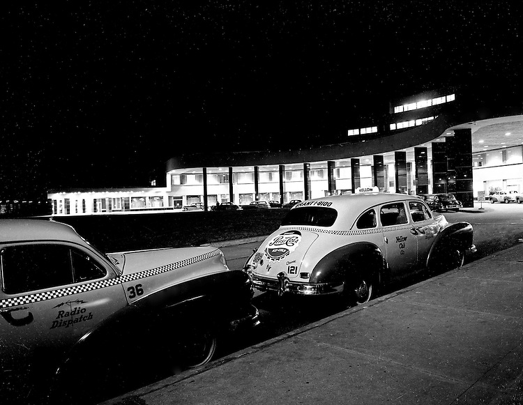Moon Township PA:  View of the main entrance and 1949 Dodge Taxi cabs waiting for a fare on opening night at the new Greater Pittsburgh Airport. <br /> <br /> In 1944, Allegheny County officials proposed to expand the military airport with the addition of a commercial passenger terminal in order to relieve the Allegheny County Airport, which was built in 1926 and whose capacity was quickly becoming insufficient to support the growing demand for air travel.  The new airport, christened as Greater Pittsburgh Airport opened on May 31, 1952. The first flight occurred on June 3, 1952.