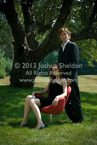 Man standing behind woman seated in red chair on lawn underneath apple tree