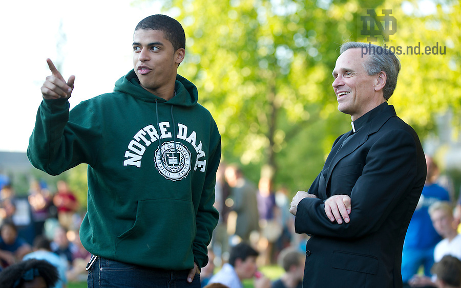 August 21, 2012; Rev. John I. Jenkins, C.S.C., president of the University of Notre Dame, chats with a student at the picnic on DeBartolo Quad, following opening Mass. Photo by Barbara Johnston/University of Notre Dame