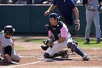 August 30, 2009: Everett AquaSox catcher Trevor Coleman blocks the plate as Salem-Keizer Volcanoes' Joel Weeks attempts to score during a Northwest League game at Everett Memorial Stadium in Everett, Washington.  The AquaSox wore pink jerseys for breast cancer awareness.