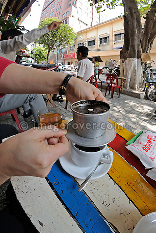 Asia, Vietnam, Ho Chi Minh City (Saigon). Enjoying a vietnamese style Hot Cafe Milk in the shopping area on Dong Khoi St.