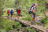 Photo story of Philmont Scout Ranch in Cimarron, New Mexico, taken during a Boy Scout Troop backpack trip in the summer of 2013. Photo is part of a comprehensive picture package which shows in-depth photography of a BSA Ventures crew on a trek.  In this photo BSA Venture Crew Scouts make their way across a makeshift  wooden bridge over a stream in the backcountry at Philmont Scout Ranch.   <br /> <br /> The  Photo by travel photograph: PatrickschneiderPhoto.com