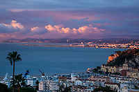 Aerial sunrise view of Nice, with the harbor neighborhood and the airport under a colorful, cloudy sky, on the French Riviera (Côte d'Azur), France