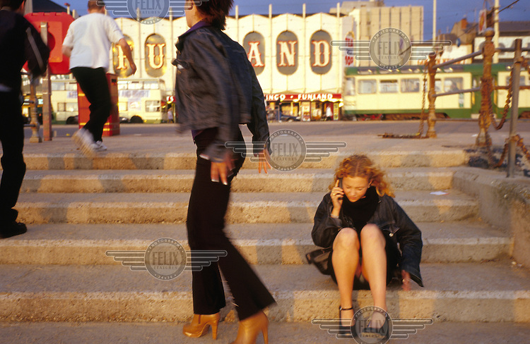 Women cast long evening shadows along Blackpool promenade as they organise the night's festivities.