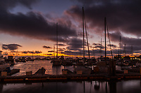 A half hour after sunset the sky glows, casting the sailboats and their masts in silhouette.