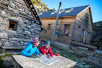 Two women sit outside the Rifugio Tomeo looking at maps, along the Via Alta Via Maggia, a difficult week long trek from Locarno to Broglio, Switzerland.
