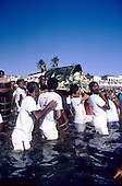 Salvador, Brazil. Festival of Iemanja - Candoble followers dressed in white carrying an offering of flowers to the sea.