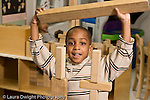 Education preschool 4 year olds block area happy boy about to place large wooden block on top of structure looking at viewer  horizontal