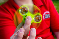 A young boy in a red school uniform plays with a green fidget spinner toy