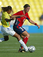 14 August 2004:  USA Abby Wambach dribbles the ball away from Brazil Defender  at Kaftanzoglio Stadium in Thessaloniki, Greece.   USA defeated Brazil, 2-0. Credit: Michael Pimentel / ISI