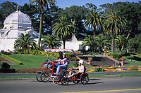 San Francisco, California - Family Recreation in Golden Gate Park, Conservatory of Flowers in the Background.  John F. Kennedy Drive is closed to motorized traffic on Sundays.