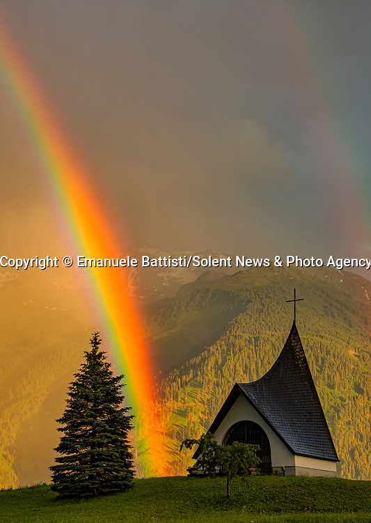 """Pictured: A magnificent rainbow stretches across the sky as it appears to emerge from a quaint chapel in the Austrian hills. <br /> <br /> The natural phenomenon was captured by mechanical engineer Emanuele Battisti as he was travelling through the countryside with his wife. <br /> <br /> The vivid colours of a single rainbow illuminate the overcast sky as the Chapel Krebsbach can be found sitting at the end of the rainbow in Barwies, Austria - only for another to appear moments later. <br /> <br /> The 43 year-old said """"I was travelling with my wife when i saw this magnificent opportunity passing us. I told my wife to get in the drivers seat so we could park and I could take some photographs"""" <br /> <br /> Originally from Italy, Mr Battisti said """"These kinds of situations do not come along very often in the lifetime of a photographer: there is no way you can plan this type of photo and I usually don't have much luck!"""" <br /> <br /> """"I was super excited because I was so lucky to be at the right time in the right place, with a magical light at the sunset.""""<br /> <br /> Please byline: Emanuele Battisti/Solent News<br /> <br /> © Emanuele Battisti/Solent News & Photo Agency<br /> UK +44 (0) 2380 458800"""