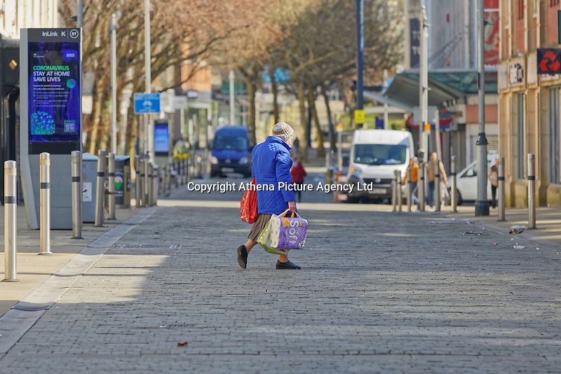 Pictured: An elderly woman with shopping in Oxford Street,  Swansea, Wales, UK. Thursday 26 March 2020<br /> Re: Covid-19 Coronavirus pandemic, UK.