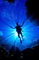 A  scuba diver in silhouette prepares to explore Hawaii's coral reefs.