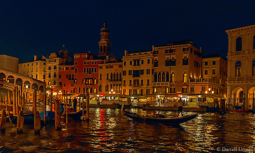 Fine Art Photograph. Night scene of a Venetian Gondolier paddling through the romantic city of Venice as the city lights are reflected around him on the Venetian waterways.