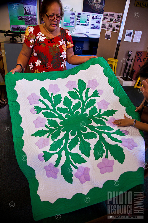 A woman showing her Hawaiian quilt at the Kauai Museum