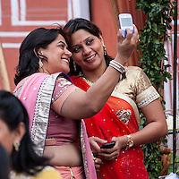 Jaipur, Rajasthan, India.  Two Indian Ladies Taking a Selfie at a Wedding Reception.