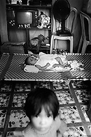 Philippines. National Capital Region. Manila. Paradise village. A young child lays down on a plastic folding bed. Paradise village has a population of 15'000 people and is a part of Barangay Tonsuya situated on Lettre Road in Malabon. Manila is part of the National Capital Region (NCR) on Luzon island. Manila is the capital of the Philippines and one of the sixteen cities that comprise Metro Manila. Metro Manila is the most populous metropolitan area in the Philippines. © 1999 Didier Ruef