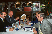 Bucharest, Romania. Businessmen and woman sitting at a table in a smart restaurant.