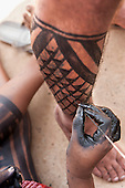 A Kayapo woman paints a visitor's leg with black Genipapo body paint at the International Indigenous Games in Brazil. 22nd October 2015