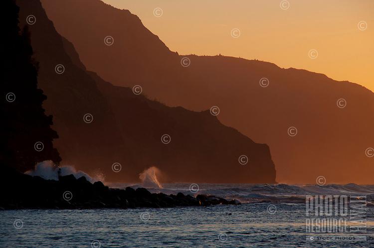 The setting sun casting a warm glow over the cliffs of Na Pali near Ke'e Beach, Kauai.