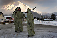 The Wild Ones don grotesque masks and suits of lichen gathered from the trees for an ancient Pagan tradition known as Schleicherlaufen held in the Tyrol of Austria since 1571.  The father and son's costumes are a symbol of winter which parallel's traditional celebration of Carnival.<br /> <br /> One of the Wild Ones, Kurt Hofer, is helped into his costume made of lichen that he'll wear in the parade.  His wife, Helga Hofer painstakingly spent three weeks making his costume by sewing each piece of lichen onto a cloth.  She has done this for Kurt and their son for ten years.