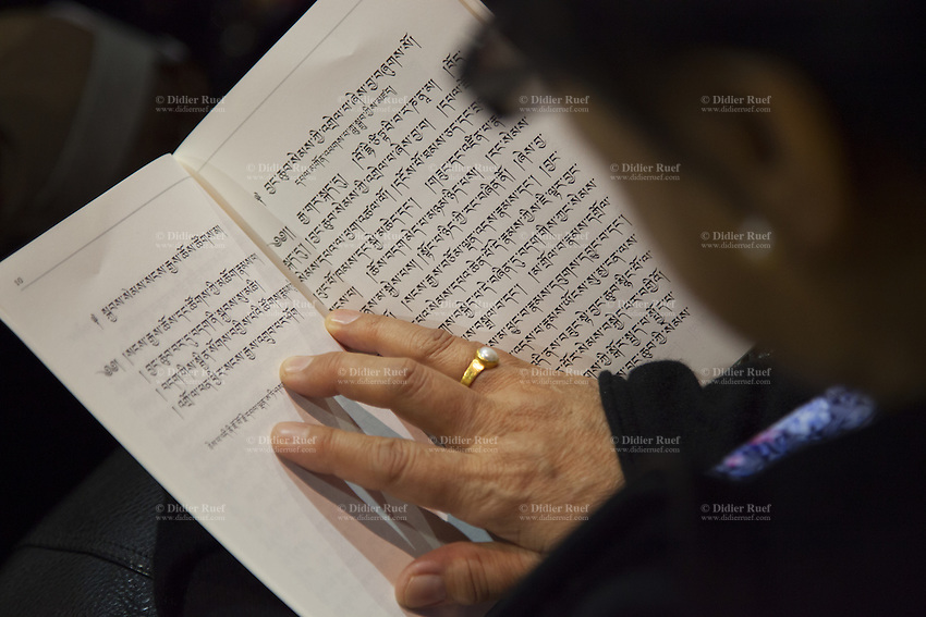 """Switzerland. Basel. St. Jakobshalle.  A woman is reading tibetan alphabet letters during a public speech by His Holiness the Dalai Lama on Bodhicitta. The lecture's topic is about Nagarjuna's Commentary on Bodhicitta which touches on two aspects of the awakening mind, the twin qualities of wisdom and compassion, which are necessary for anyone who aspires to be a better person and implement changes in their lives. The 14th and current Dalai Lama is Tenzin Gyatso, recognized since 1950. He is the current Dalai Lama, as well as the longest-lived incumbent, well known for his lifelong advocacy for Tibetans inside and outside Tibet. Dalai Lamas are amongst the head monks of the Gelug school, the newest of the schools of Tibetan Buddhism. The Dalai Lama, also called """" Ocean of Wisdom"""" is considered as the incarnation of Chenresi, the Bodhisattva of compassion who is also the protective deity of Tibet. 7.02.2015 © 2015 Didier Ruef"""