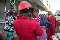 During an eviction, Red Ant William Mahlalela plays with S'nehlanhla Fortunate Majoro as her mother atempts to gather together some of her belongings after they were evicted from Fatti's Mansions in Johannesburg. <br /><br /><br />The Red Ants are a controversial private security company often hired to clear squatters from land and so-called 'hijacked' properties.