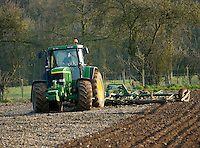 Photo: Richard Lane/Richard Lane Photography..A John Deere 7810 tractor pulls a 6 metre trailed sping tine cultivator in a field in the Chiltern Hills near Beaconsfield, South Buckinghamshire. 09/04/2004.