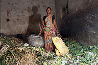 Sara Swati Mondol, 45, stands in a refuse collection point in the Kolay Market in Kolkata. She collects discarded plastic which she later resells in her village. She has been doing this job since childhood and earns around $1 per day. Many millions of Indian people still live below the poverty line and are often the most vulnerable to pollution. India. November, 2013
