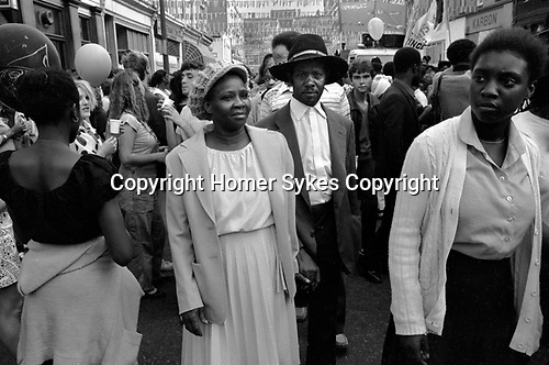 Black older couple in crowd at the 1981 Notting Hill Carnival 1980s UK