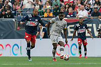 FOXBOROUGH, MA - JULY 25: Victor Wanyama #2 of CF Montreal passes the ball as Teal Bunbury #10 of New England Revolution defends during a game between CF Montreal and New England Revolution at Gillette Stadium on July 25, 2021 in Foxborough, Massachusetts.