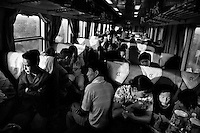Travelers sit and sleep in a crowded hard-seat passenger train car in Gansu Province, China.