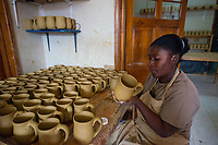 Haiti, Port-au-Prince. Artisan business, Papillon. Produce ceramics, jewelry, t-shirts. Over 300 women on payroll (men work her as well), making about $15 a day. Women working in ceramics.