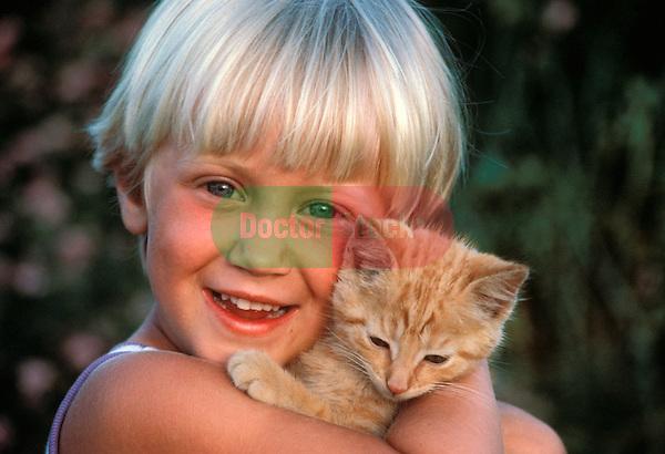 smiling young girl holding kitten