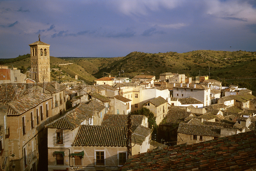City scene, tile rooftops and hills across River Tajo. Tower at left is Church of San Miguel. Toledo Castilla-La Mancha Spain.