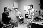 Young male doctor listening to middle age male patient in examination room as he describes condition