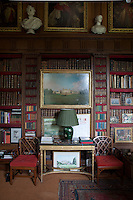 A painting of Badminton House by Canaletto hangs from the bookcase in the library, while the table below is flanked by Chinese Chippendale chairs by John Linnell