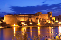 The chateau in Collioure harbour. Collioure. Roussillon. France. Europe. Evening light with a radiant blue sky. Night time illumination.