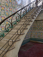 An elaborate floral motif decorates the tiled walls of this staircase which is framed by a wrought-iron hand rail