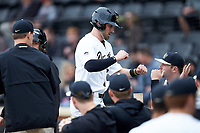 Jake Mueller (23) of the Wake Forest Demon Deacons is greeted by his teammates as he returns t the dugout after scoring a run against the Sacred Heart Pioneers at David F. Couch Ballpark on February 15, 2019 in  Winston-Salem, North Carolina.  The Demon Deacons defeated the Pioneers 14-1.  (Brian Westerholt/Four Seam Images)